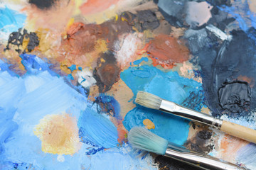 Colorful artist's palette with oil paint strokes.