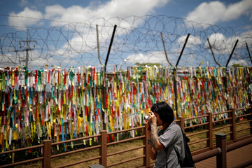 A woman takes a photograph of a barbed-wire fence decorated with ribbons bearing messages wishing for the two Korea's unification near the demilitarized zone in Paju