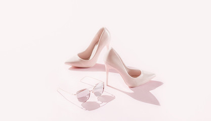 Pink female high heels/shoes on pink background.