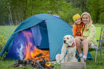 Family tourist near his camp tent at campfire with dog.