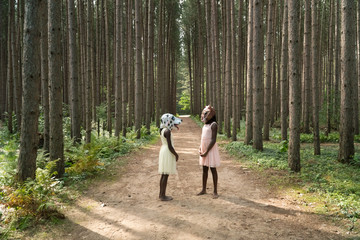 Two African American girls wearing dog and squirtrel masks in a