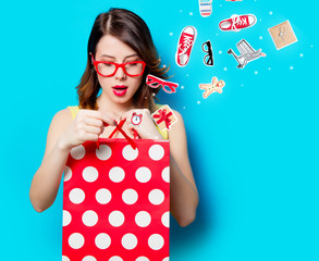 portrait of beautiful surprised young woman with shopping bag on the wonderful blue studio background with clothes