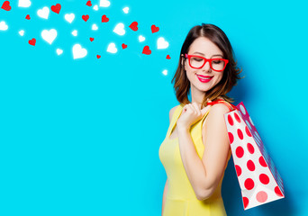 portrait of beautiful young woman with shopping bag on the wonderful blue studio background and abstract hearts