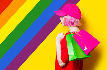 portrait of beautiful young woman with shopping bags on the wonderful yellow studio background with rainbow
