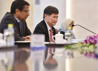 Association of South East Asian Nations (ASEAN) Secretary-General Lim Jock Hoi listens to Chinese Foreign Minister Wang Yi during a meeting at the Foreign Ministry in Beijing
