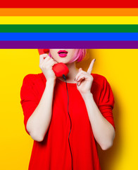 portrait of beautiful surprised young woman with red handset on the wonderful yellow studio background with rainbow