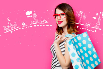 portrait of beautiful young woman with shopping bag on the wonderful pink studio background and travel route
