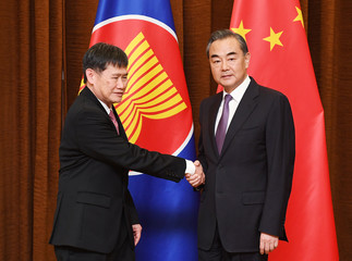 Association of South East Asian Nations (ASEAN) Secretary-General Lim Jock Hoi (L) is greeted by Chinese Foreign Minister Wang Yi before a meeting at the Foreign Ministry in Beijing