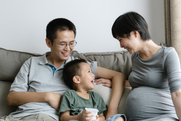 Little boy] with dad and pregnant mom at home