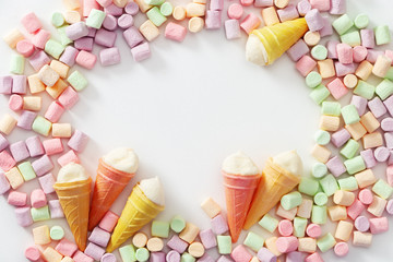 Frame of  multicolored mini marshmallow and ice cream cones  on light background. Copy space. Top view.