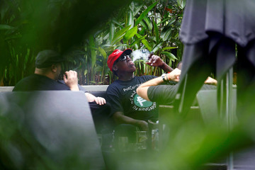 Former U.S. basketball star Dennis Rodman smokes a cigar at the poolside of Regent Hotel in Singapore