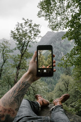 Anonymous male tattooed hand and feet in  leather boots lying in jungle and taking photo with smartphone