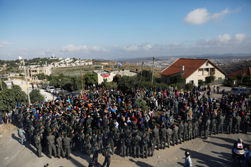 Israeli security forces gather around protestors as they come to evacuate 15 Jewish settler families from the illegal outpost of Netiv Ha'avot in the Israeli occupied West Bank