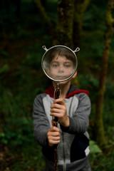 boy looking through sieve