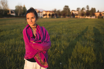 Woman in fuchsia scarf relaxing at sunset
