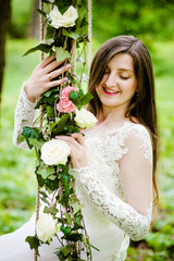 Dreamy bride is sitting on a swing decorated with flowers in the park
