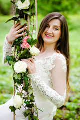 Beautiful bride is sitting on a swing decorated with flowers in the park