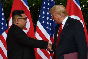 U.S. President Donald Trump and North Korea's leader Kim Jong Un shake hands during their summit at the Capella Hotel on Sentosa island in Singapore