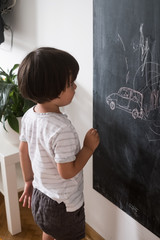 Toddler Drawing  A Car On The Blackboard