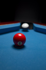 Red and white billiard balls over blue felt