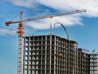 Construction crane and concrete building under construction against blue sky. Construction site.