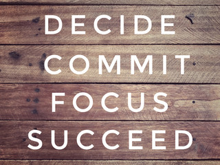 Motivational and inspirational quote - ' Decide, commit, focus, succeed' on a wooden wall. With vintage styled background.