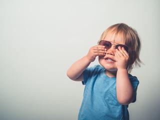Little toddler boy in sunglasses on white