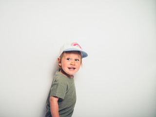 Cute little boy with hat posing on white