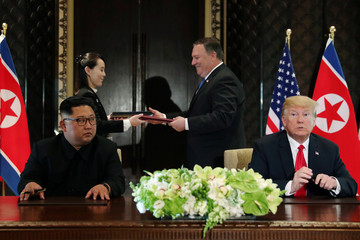 North Korea's leader Kim Jong Un looks at U.S. President Donald Trump as Kim's sister Kim Yo Jong exchanges document with U.S. Secretary of State Mike Pompeo at their summit in Singapore