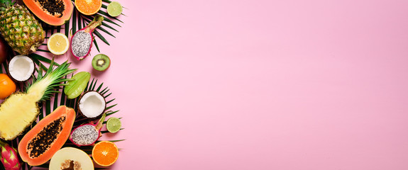 Exotic fruits and tropical palm leaves on pastel pink background - papaya, mango, pineapple,...
