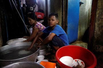 Children wash dishes at the back of a tea shop in Yangon