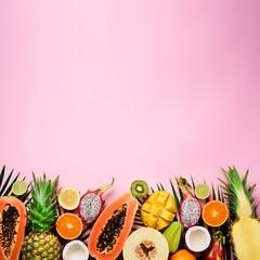 Exotic fruits and tropical palm leaves on pastel pink background - papaya, mango, pineapple, banana, carambola, dragon fruit, kiwi, lemon, orange, melon, coconut, lime. Top view.