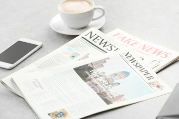 Morning newspapers, cup of hot coffee and phone on grey table