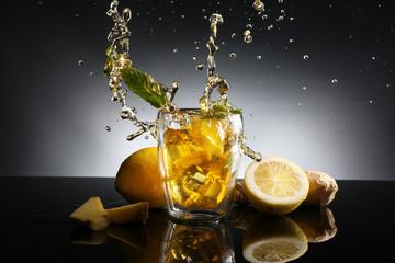 Printed roller blinds Splashing water Glass of lemon tea with splash on dark background