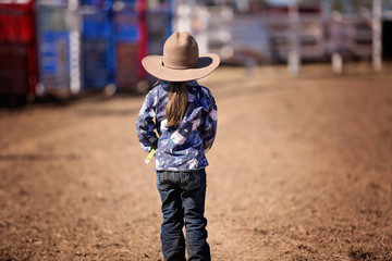Little Cowgirl Stands In The Dust Watching A Country Rodeo