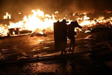 Two men protect themselves with a piece of wood as they run next to a fire at a market in Port-au-Prince