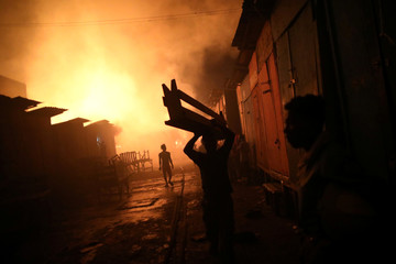 A man carries a bench out of a fire at a market in Port-au-Prince