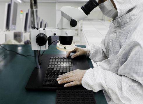 Image not clear of Engineer wear gloves using microscopy for examination BGA for quality control,Semiconductor hi tech industry, blurred background