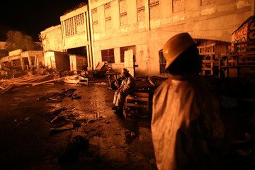 A firefighter takes a break during a fire at a market in Port-au-Prince