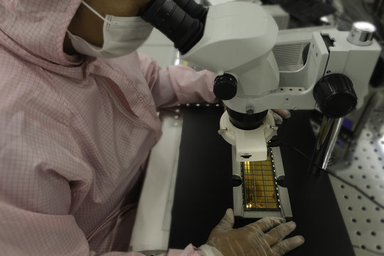 image of Workers in clean pink suits examination a silicon wafers for production by Microscopy , select focus ,semiconductor