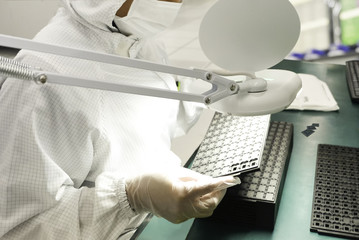 Wall Mural - hi-tech industry, Engineer in white gloves using magnifying lamp for inspection IC before packing at clean room in semiconductor, blurred background and light reflector  from magnifying lamp