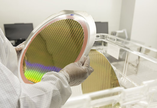 Hands of Engineer in white gloves holding a Silicon wafers inspection at  a clean room semiconductor, light blue and green reflections of a silicon wafer reflecting colors ,blurred background