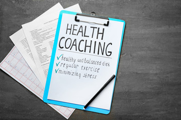 Health coaching written on sheet of paper with medical documents on grey background