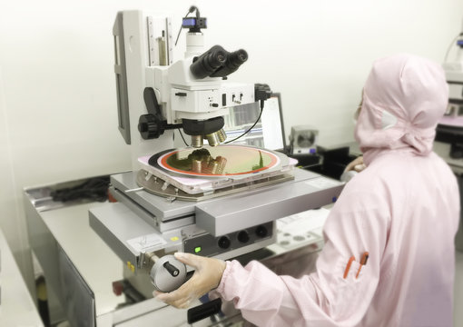 image not clear of engineer working in white gloves using a microscope for examination a silicon wafer, Reflection light and blurred background