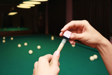 Billiard player rubs chalk his cue. Details of the game of billiards.