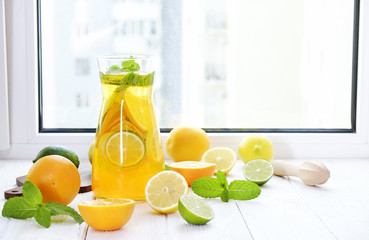 Iced lemonade pitcher, wooden juicer, cold citrus infused water with lemon & lime slices, mint leaves, cutting board on white wooden windowsill. Apartment window background, close up, copy space.