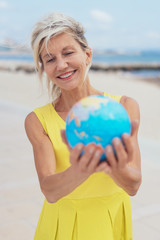 Happy blond woman holding a world globe