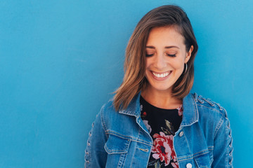 Pretty, young smiling woman with blue copy space