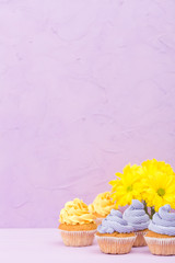 Cupcakes decorated with yellow and violet cream and bouquet of chrysanthemums on violet pastel background with text area for greeting banner.