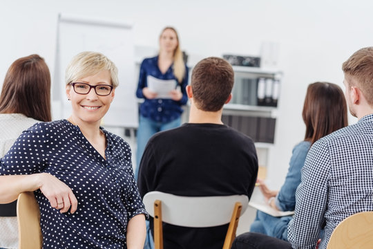 Woman smiling at camera during office meeting